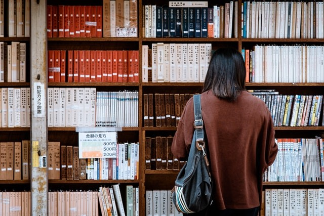 Image source - https://www.pexels.com/photo/woman-wearing-brown-shirt-carrying-black-leather-bag-on-front-of-library-books-1106468/